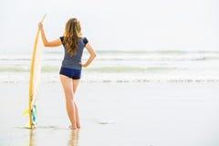 Όμορφες νέες παραμονές κοριτσιών surfer στην παραλία Στοκ εικόνες με δικαίωμα ελεύθερης χρήσης