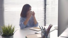 Όμορφες νεολαίες που χαμογελούν την ασιατική γυναίκα που εργάζεται στον υπολογιστή και τον καφέ κατανάλωσης στο καθιστικό στο σπί απόθεμα βίντεο