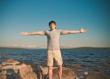 Όμορφες νεολαίες ατόμων τα υπαίθρια χέρια που αυξάνονται που στέκονται Στοκ Φωτογραφία
