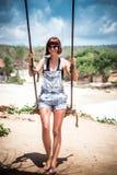 όμορφες νεολαίες γυναικών διακοπών λιμνών έννοιας Νέα ταλάντευση γυναικών σε μια ταλάντευση παραλιών στον απότομο βράχο Εκλεκτική Στοκ Εικόνα