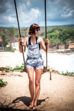 όμορφες νεολαίες γυναικών διακοπών λιμνών έννοιας Νέα ταλάντευση γυναικών σε μια ταλάντευση παραλιών στον απότομο βράχο Εκλεκτική Στοκ Φωτογραφία