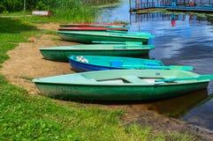 Όμορφες ξύλινες πολύχρωμες βάρκες με τα κουπιά στην παραλία για τους περιπάτους κατά μήκος του ποταμού, λίμνη, θάλασσα, ωκεανός σ στοκ εικόνες