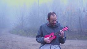 Όμορφες πέρκες παιχνιδιού ατόμων πορτρέτου ukulele στο πάρκο, έννοια μουσικής απόθεμα βίντεο