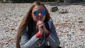 Όμορφες στάσεις οκλαδόν νέων κοριτσιών στην παραλία στην παραλία χαλικιών απόθεμα βίντεο