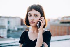 Όμορφες συζητήσεις κοριτσιών στο τηλέφωνο στο ηλιοβασίλεμα στοκ φωτογραφίες