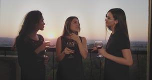 Όμορφες τρεις κυρίες στην κορυφή του κτηρίου στο μπαλκόνι έχουν ένα κόμμα κοριτσιών που πίνουν κάποιο κρασί γυαλιού και έχουν το  φιλμ μικρού μήκους