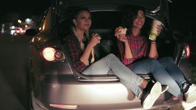 Όμορφες φίλες που κάθονται στον ανοικτό κορμό του αυτοκινήτου, που μιλούν και που τρώνε τα σάντουιτς, που πίνουν από το φλυτζάνι  απόθεμα βίντεο