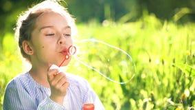 Όμορφες φυσαλίδες σαπουνιών μικρών κοριτσιών φυσώντας στη θερινή ημέρα απόθεμα βίντεο
