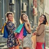 Όμορφες χαμογελώντας φίλες με τις αγορές στοκ φωτογραφίες