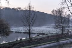 Όμορφη άποψη μιας λίμνης και ενός χιονιού στη χλόη στον τομέα στοκ εικόνα