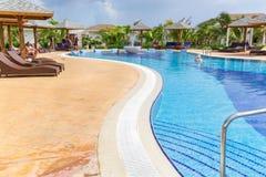 Όμορφη άποψη πρόσκλησης της άνετης άνετης κυρτής πισίνας με τους ανθρώπους που χαλαρώνουν, που κολυμπούν και που απολαμβάνουν το  Στοκ φωτογραφία με δικαίωμα ελεύθερης χρήσης
