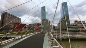 Όμορφη άποψη σχετικά με τα ειρηνικές κτήρια και τη γέφυρα Zubizuri στο Μπιλμπάο, Ισπανία απόθεμα βίντεο