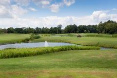 Όμορφη άποψη σχετικά με το γήπεδο του γκολφ με την τέλειες χλόη και τη λίμνη στοκ φωτογραφία με δικαίωμα ελεύθερης χρήσης