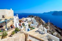 Όμορφη άποψη σχετικά με το παλαιό φρούριο του νησιού Santorini Oia στην πόλη και των τουριστών που περπατούν γύρω Στοκ Φωτογραφία