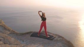 Όμορφη άποψη της γυναίκας που κάνει το τέντωμα γιόγκας στο βουνό με την άποψη θάλασσας στο ηλιοβασίλεμα Τεντώνοντας όπλα φιλμ μικρού μήκους