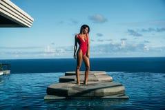 Όμορφη άποψη της προκλητικής χαλάρωσης κοριτσιών στην πισίνα με τον ωκεανό στο υπόβαθρο Χαριτωμένη νέα γυναίκα στην κόκκινη τοποθ Στοκ Φωτογραφία