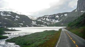 Όμορφη άποψη τοπίων και τοπίου της Νορβηγίας, των λόφων και του βουνού που καλύπτονται μερικώς με το άσπρες χιόνι και τη λίμνη στοκ εικόνα με δικαίωμα ελεύθερης χρήσης