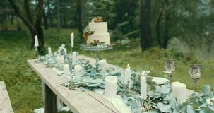 Όμορφη άποψη του ρομαντικού ντεκόρ ημερομηνίας του πίνακα Καλύπτεται με τα κεριά αστραπής, leves, τα λουλούδια και νόστιμα δύο απόθεμα βίντεο