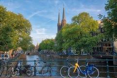 Όμορφη άποψη των καναλιών του Άμστερνταμ με τη γέφυρα και χαρακτηριστικά ολλανδικά στοκ εικόνα