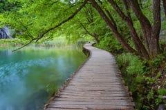 Όμορφη άποψη των καταρρακτών με το τυρκουάζ νερό και την ξύλινη διάβαση μέσω πέρα από το νερό εθνικό plitvice πάρκων λιμνών της Κ Στοκ εικόνες με δικαίωμα ελεύθερης χρήσης