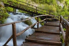 Όμορφη άποψη των καταρρακτών με το τυρκουάζ νερό και την ξύλινη διάβαση μέσω πέρα από το νερό εθνικό plitvice πάρκων λιμνών της Κ Στοκ Εικόνα