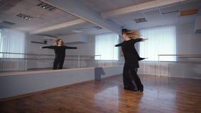 Όμορφη άσπρος-μαλλιαρή γυναίκα στο μαύρο κοστούμι μεταξιού που χορεύει στην τάξη με την μπάρα μπαλέτου και τον καθρέφτη στους τοί απόθεμα βίντεο