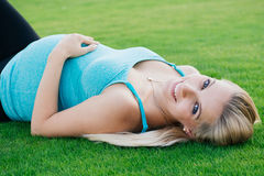 Όμορφη έγκυος γυναίκα που βάζει στη χλόη Στοκ εικόνες με δικαίωμα ελεύθερης χρήσης