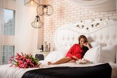 Όμορφη έγκυος γυναίκα που βρίσκεται στο κρεβάτι με μια ανθοδέσμη των λουλουδιών και των γλυκών στοκ φωτογραφία με δικαίωμα ελεύθερης χρήσης