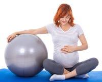 Όμορφη έγκυος γυναίκα που κάνει τις ασκήσεις με απομονωμένο το fitball ο Στοκ Εικόνα