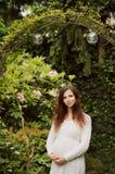 Όμορφη έγκυος γυναίκα που στέκεται στον κήπο στοκ εικόνα με δικαίωμα ελεύθερης χρήσης