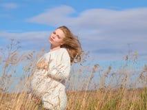 Όμορφη έγκυος γυναίκα σε ένα άσπρο μάλλινο πουλόβερ στοκ εικόνες