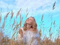 Όμορφη έγκυος γυναίκα στην υψηλή ξηρά χλόη ενάντια στο μπλε ουρανό στοκ εικόνες