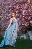Όμορφη έγκυος γυναίκα στον ανθίζοντας κήπο Στοκ Φωτογραφία