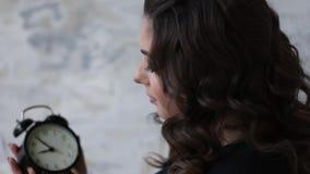 Όμορφη έγκυος γυναίκα στο μαύρο κομπινεζόν Κρατά το ρολόι στη συμβολική υπόδειξη χεριών στο remanining χρόνο befour φιλμ μικρού μήκους