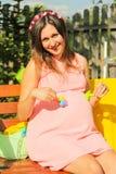 Όμορφη έγκυος γυναίκα υπαίθρια με τις διακοσμήσεις Στοκ Εικόνες