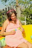 Όμορφη έγκυος γυναίκα υπαίθρια με τις διακοσμήσεις Στοκ εικόνα με δικαίωμα ελεύθερης χρήσης