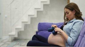 Όμορφη έγκυος νέα γυναίκα που κρατά ένα ζευγάρι των χαριτωμένων καλτσών μωρών γυμνό σε tummy της, που βρίσκεται στο κρεβάτι της σ απόθεμα βίντεο