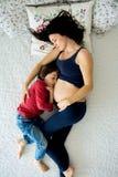 Όμορφη έγκυος νέα μητέρα και το παιδί της, αγόρι, που βρίσκονται στο κρεβάτι στοκ εικόνες