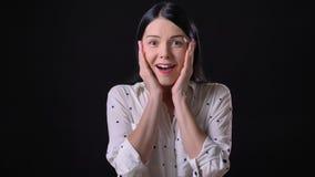 Όμορφη έκπληκτη γυναίκα που εξετάζει τη κάμερα με τις θετικές συγκινήσεις, που απομονώνονται στο μαύρο υπόβαθρο στούντιο απόθεμα βίντεο