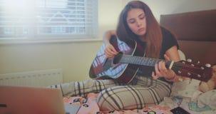 Όμορφη έναρξη κοριτσιών εφήβων να παίζουν στην κιθάρα στην κρεβατοκάμαρά της, φθορά πυτζάμες έχει λίγο της χαλάρωσης του χρόνου γ απόθεμα βίντεο