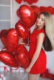 Όμορφη έξυπνη γυναίκα με τα κόκκινα μπαλόνια την ημέρα βαλεντίνων ` s Στοκ Φωτογραφίες