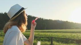Όμορφη έφηβη με καπέλο που φυσάει σαπουνόπερες απόθεμα βίντεο