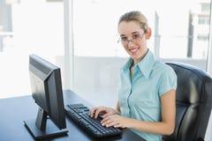 Όμορφη ήρεμη επιχειρηματίας που εργάζεται στον υπολογιστή της που χαμογελά στη κάμερα Στοκ Φωτογραφίες