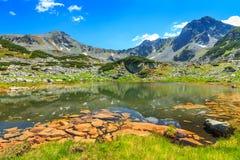 Όμορφη λίμνη παγετώνων και ζωηρόχρωμες πέτρες, βουνά Retezat, Τρανσυλβανία, Ρουμανία Στοκ φωτογραφία με δικαίωμα ελεύθερης χρήσης