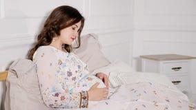 Όμορφη αγκαλιά εγκύων γυναικών στο κρεβάτι στοκ εικόνες με δικαίωμα ελεύθερης χρήσης