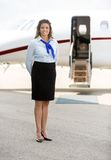 Όμορφη αεροσυνοδός που στέκεται ενάντια στο ιδιωτικό αεριωθούμενο αεροπλάνο Στοκ Φωτογραφίες