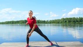 Όμορφη, αθλητική νέα ξανθή γυναίκα που κάνει τις διαφορετικές ασκήσεις Λίμνη, ποταμός, μπλε ουρανός και δάσος στο υπόβαθρο απόθεμα βίντεο