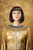 Όμορφη αιγυπτιακή γυναίκα όπως την Κλεοπάτρα στο χρυσό υπόβαθρο Στοκ Εικόνα