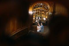 Όμορφη ακριβώς τοποθέτηση παντρεμένων ζευγαριών στα καταπληκτικά παλαιά σκαλοπάτια με το υπόβαθρο του βασιλικού ξύλινου εκλεκτής  Στοκ Εικόνες