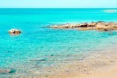 Όμορφη ακτή με τους βράχους και την άμμο, διαφανές μπλε θαλάσσιο νερό Στοκ εικόνα με δικαίωμα ελεύθερης χρήσης